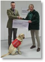 Pauline Brown of Buckingham Garden Centre hands over a cheque to Daniel Howard of Medidogs